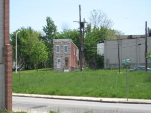 Photograph of a single remaining row house on a Baltimore street by Justin Hollander
