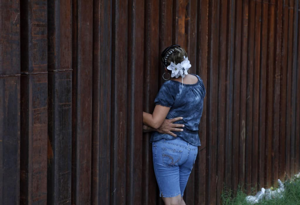 A woman, who declined to give her name, is hugged by her husband as they chat between the border fence separating Nogales, Ariz., and Nogales, Sonora, Mexico, Wednesday, July 28, 2010. A federal judge on Wednesday blocked the most controversial parts of Arizona's immigration law from taking effect, delivering a last-minute victory to opponents of the crackdown. The overall law will still take effect Thursday, but without the provisions that angered opponents — including sections that required officers to check a person's immigration status while enforcing other laws. (AP Photo/Jae C. Hong)